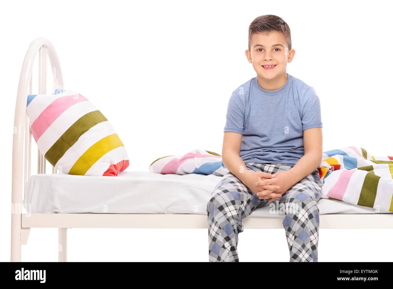 5c15d8d08d Niño en pijama azul sentado en una cama y mirando la cámara aislado en  blanco Imagen