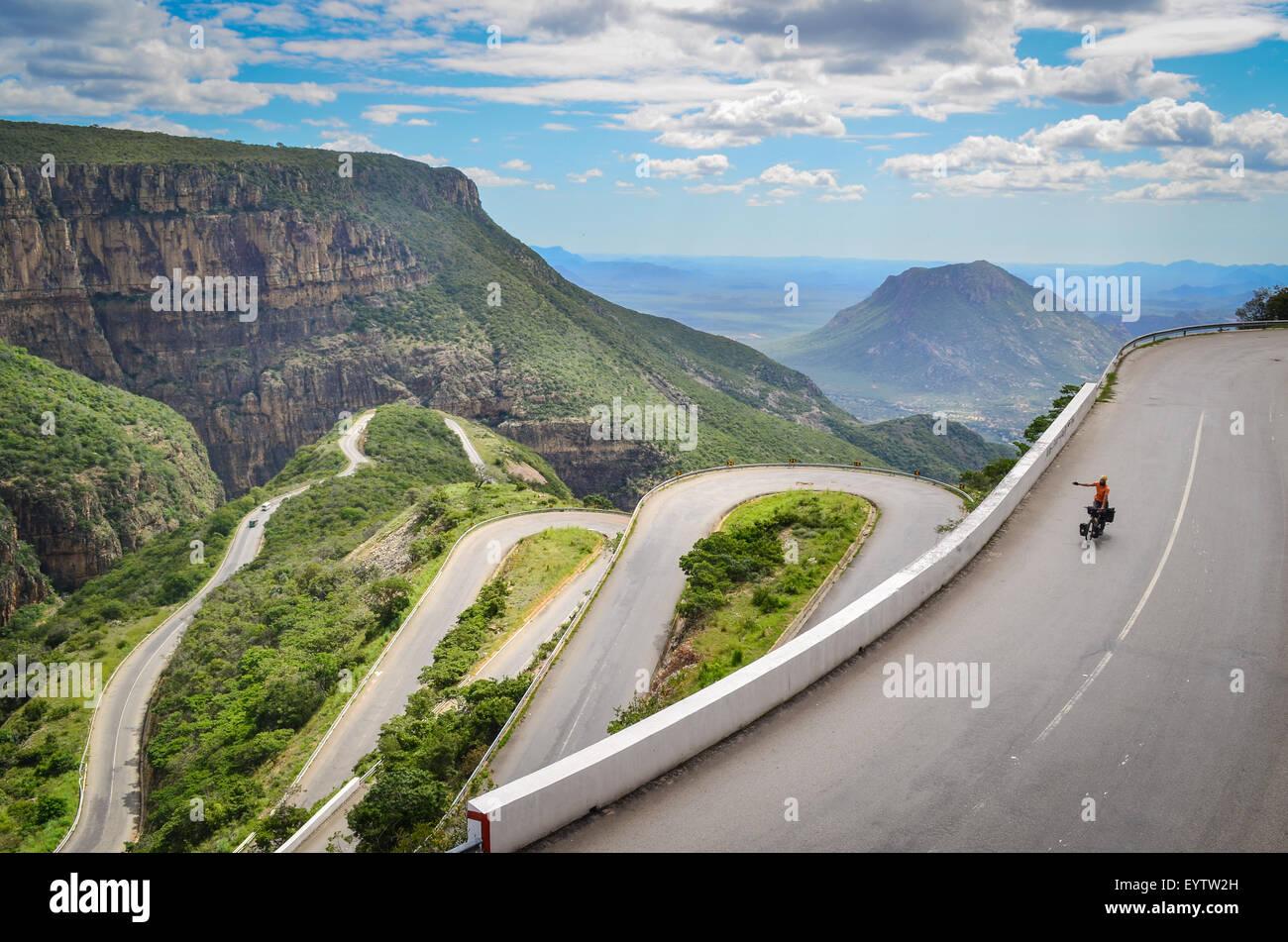 Ciclista en Serra da Leba, una cordillera en Angola con el impresionante Leba carretera de montaña y sus curvas Imagen De Stock