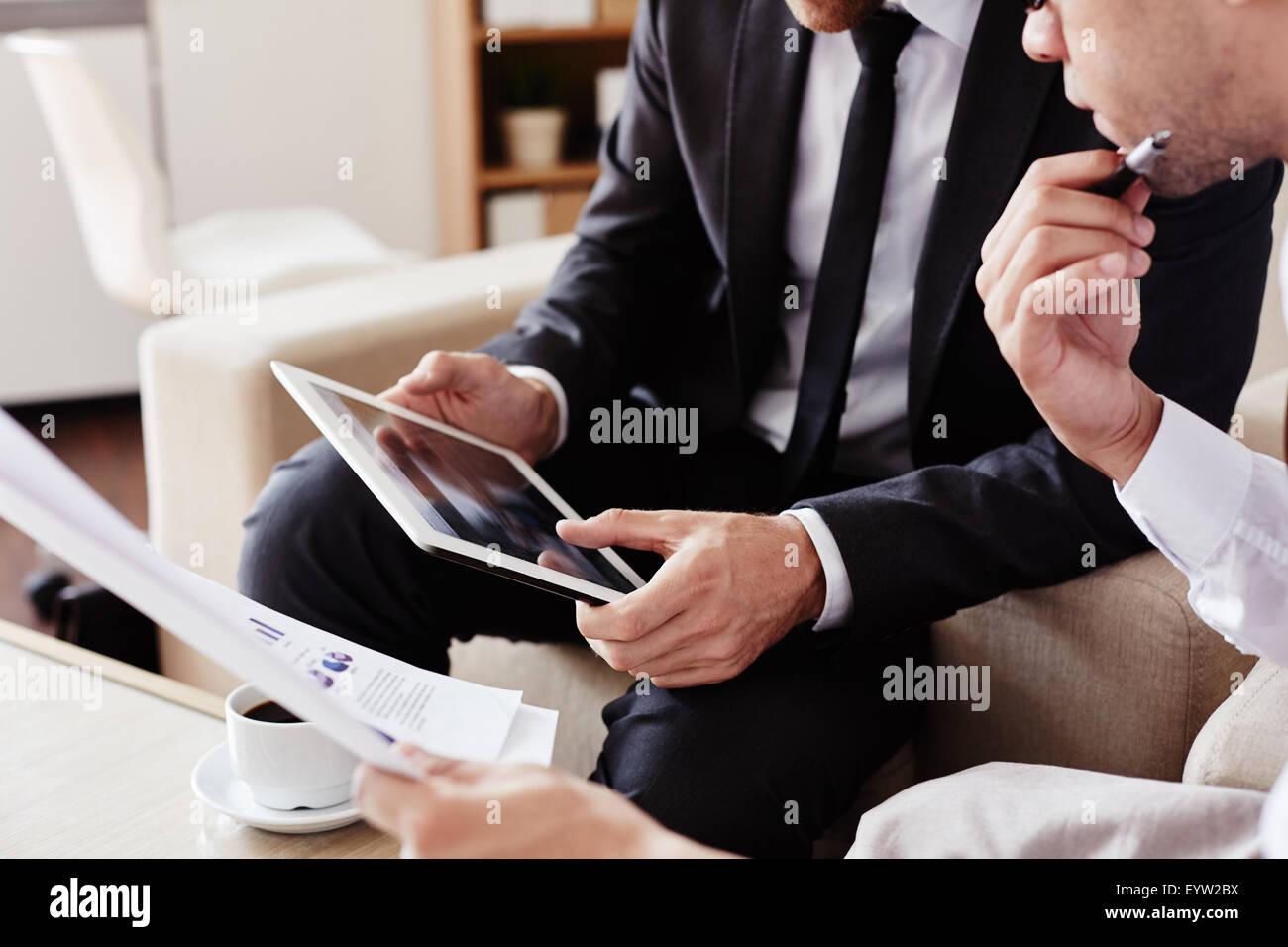 Los empleados de sexo masculino con panel táctil en reunión Imagen De Stock