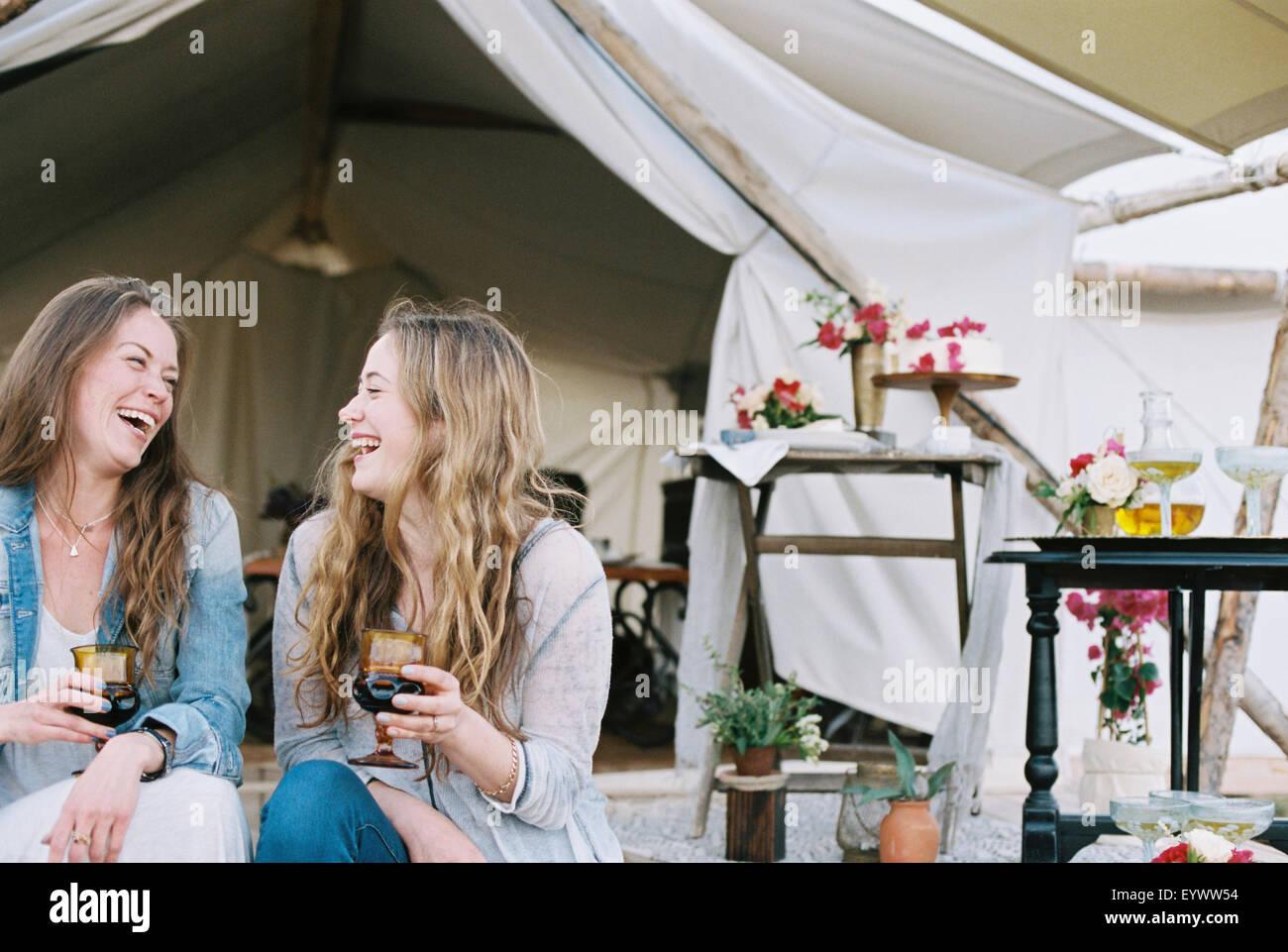 Dos mujeres sentadas sonriente fuera de una tienda de campaña en un desierto, disfrutando de una copa de vino. Imagen De Stock