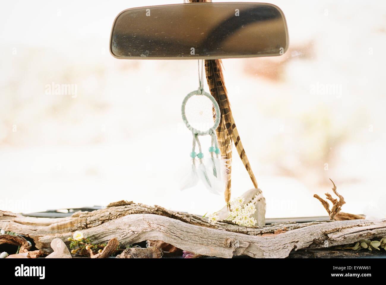 Cierre interior de un coche, Driftwood en el salpicadero, un Dream Catcher y plumas que cuelgan del retrovisor. Imagen De Stock