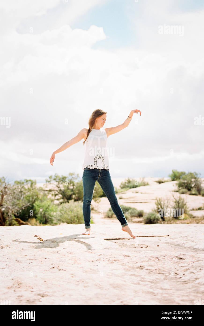 Barefoot mujer vaqueros sus brazos levantados. Imagen De Stock