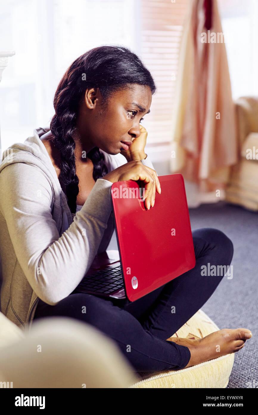 Frustrado chica étnicos sat interiores Foto de stock