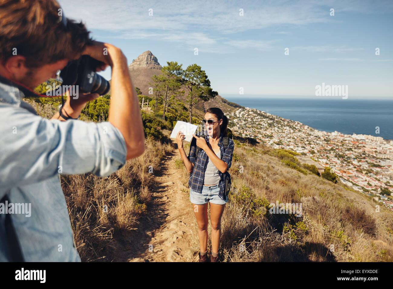 Emocionada joven Mostrar mapa y posando para su novio tomando fotos con su cámara digital. Pareja joven senderismo Imagen De Stock