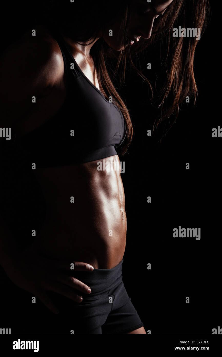 Imagen recortada del musculoso joven posando en ropa deportiva. Colocar modelo femenino con el torso perfecto en Imagen De Stock