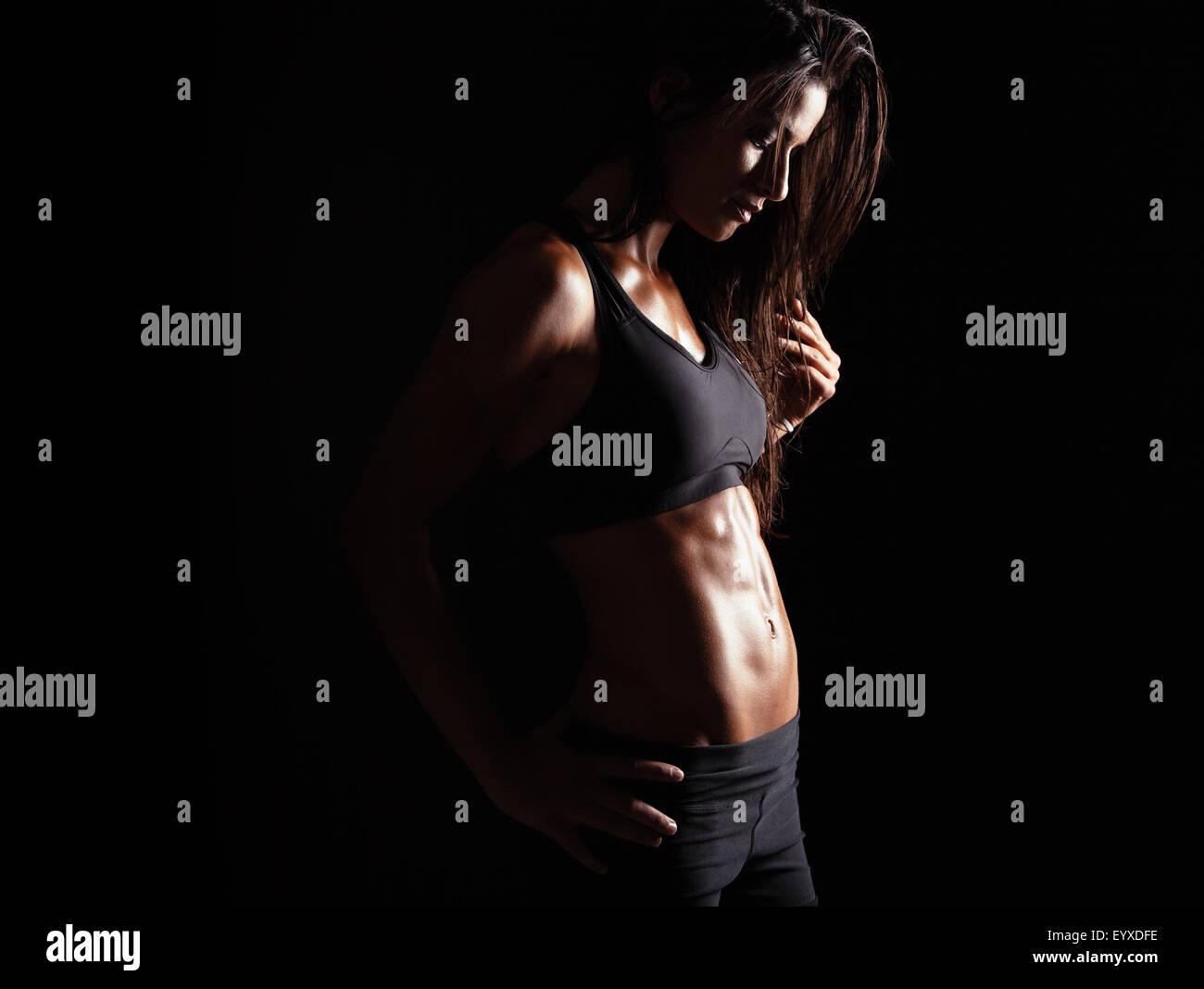 Imagen de mujeres en ropa deportiva relajante después de entrenar sobre fondo negro. Muscular con el sudor Imagen De Stock