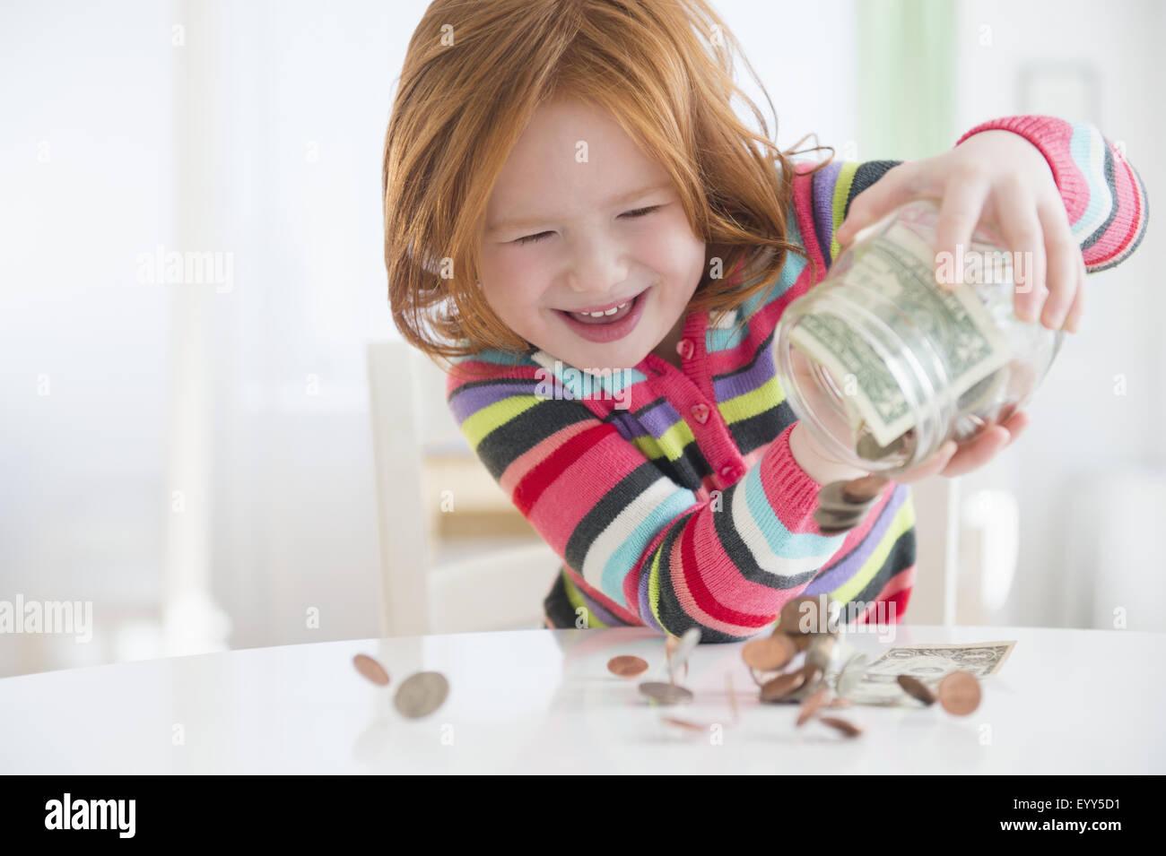 Chica caucásica meterle dinero del cambio jar Foto de stock
