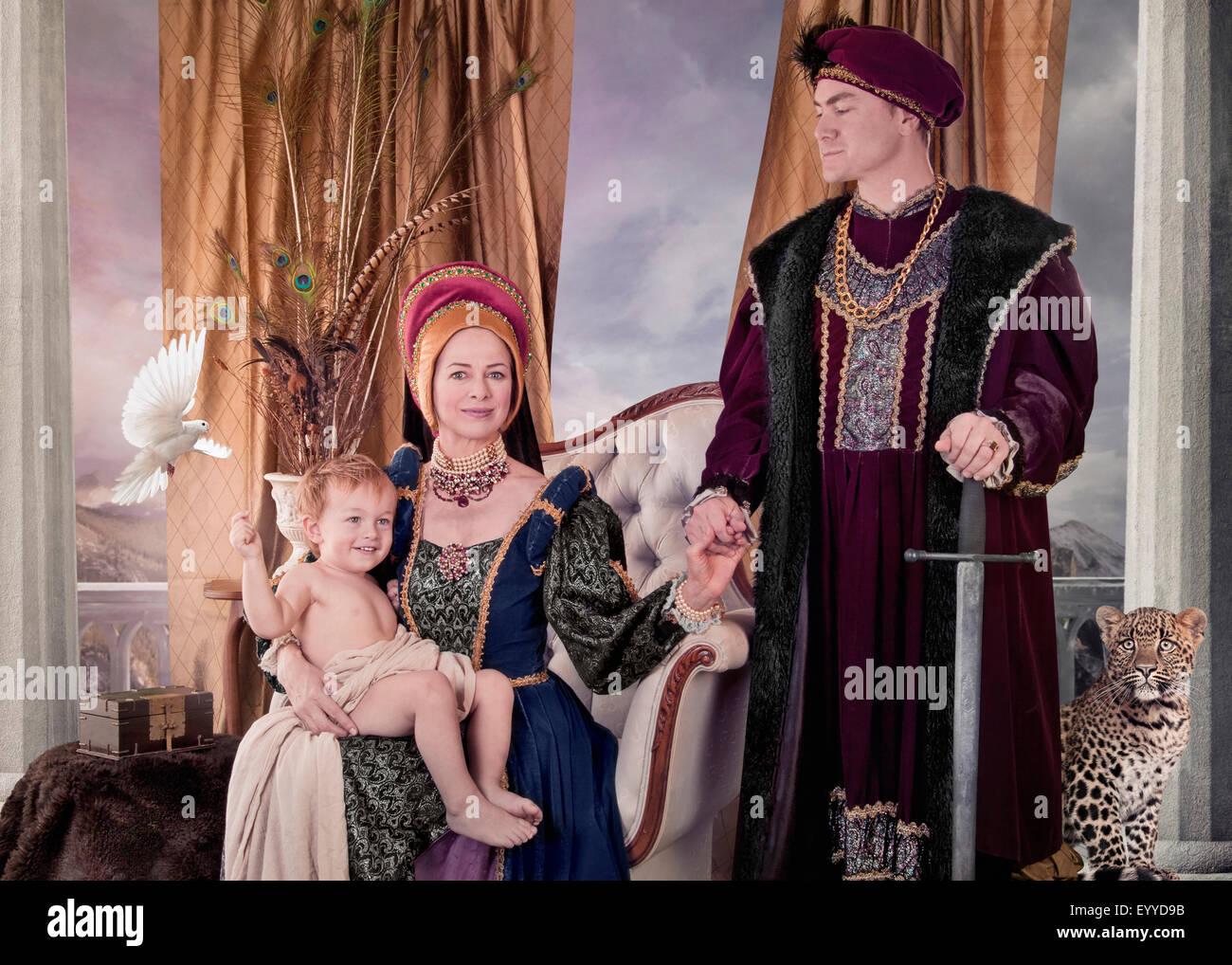 Pareja medieval y niño posando en el salón Foto de stock