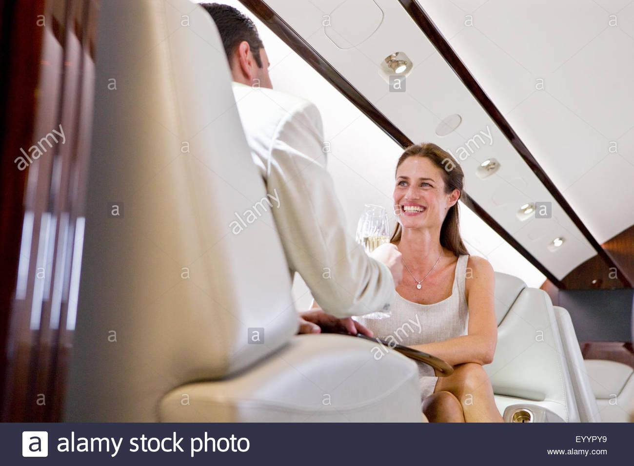 Atractiva pareja sonriente beber champán en jet privado Imagen De Stock