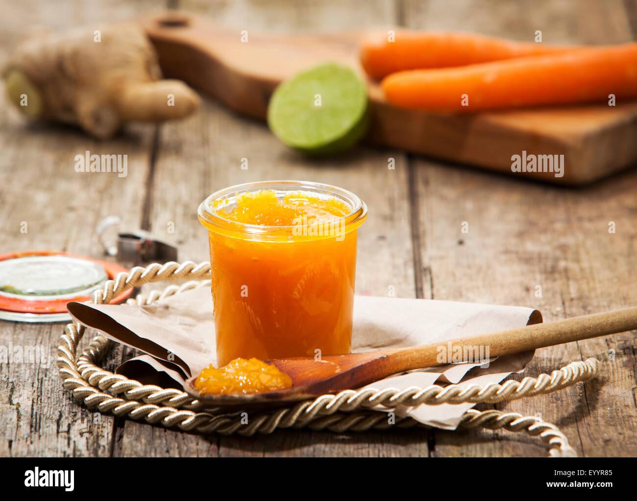 Chutney casero de zanahoria, limón y jengibre en una jarra, ingredientes en segundo plano. Imagen De Stock