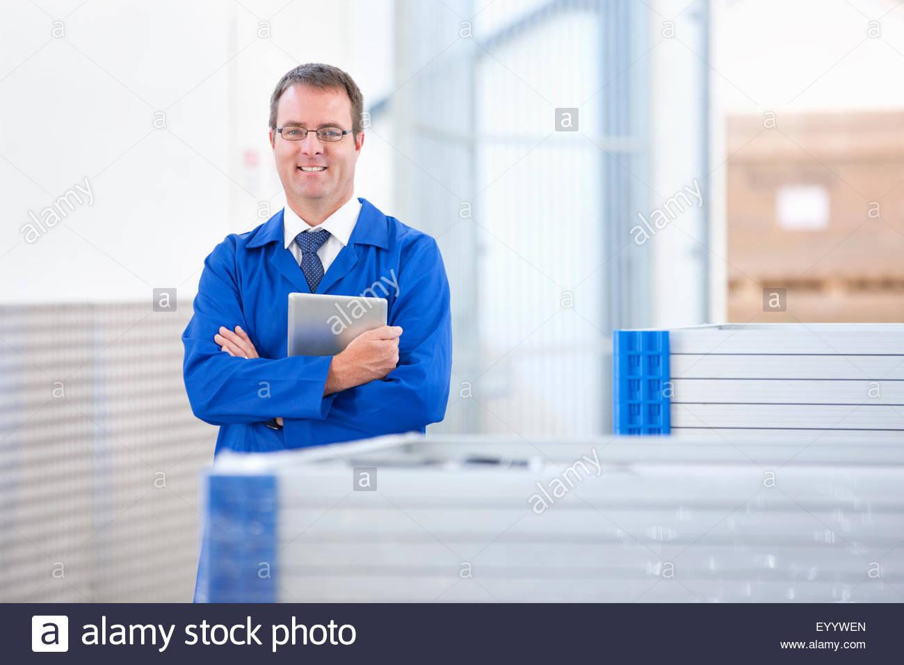 Trabajador Supervisor sonriendo ante la Cámara Control de stock de paneles solares en fábrica Imagen De Stock