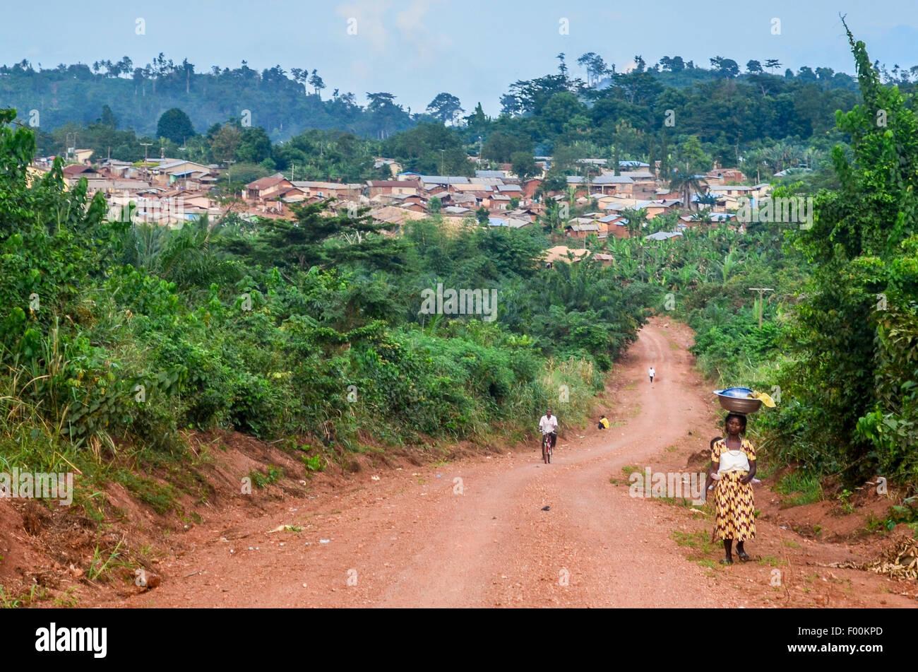 Las mujeres portadoras de cosas en la cabeza en un camino de tierra cerca de una aldea Ashanti en Ghana Foto de stock
