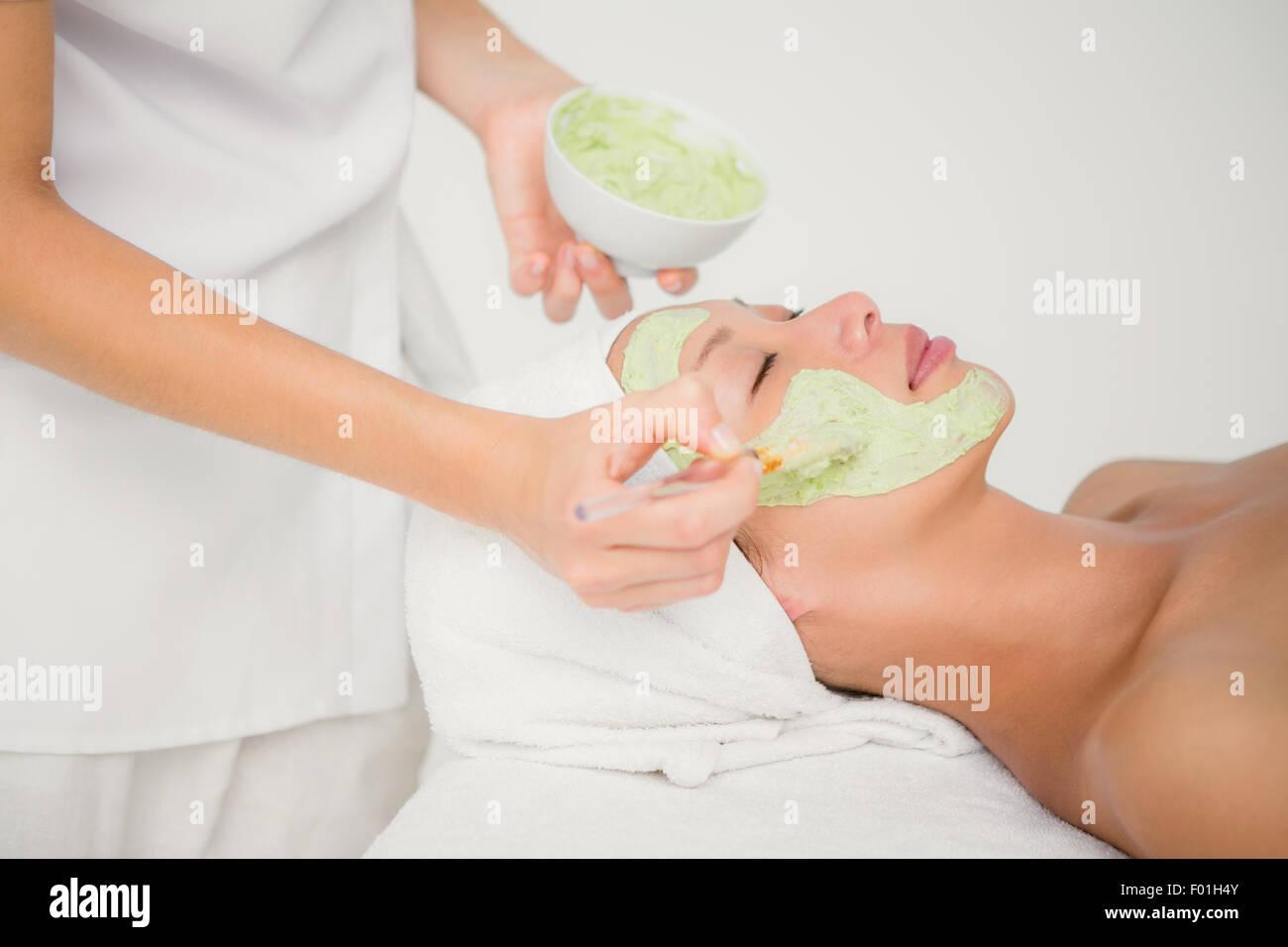 Hermosa morenita recibiendo un tratamiento facial Imagen De Stock