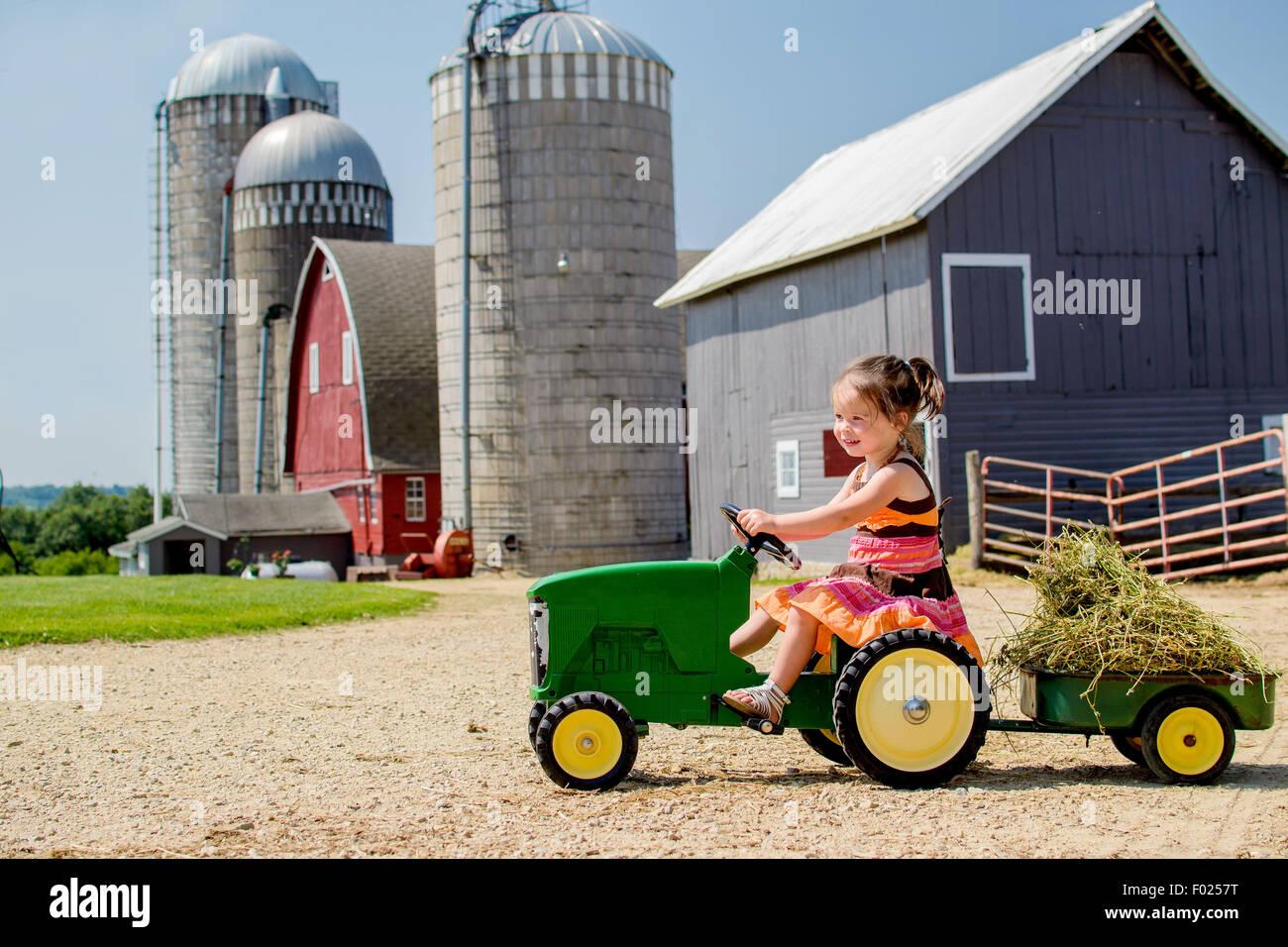 Edad elemental chica conduce su tractor de juguete Imagen De Stock
