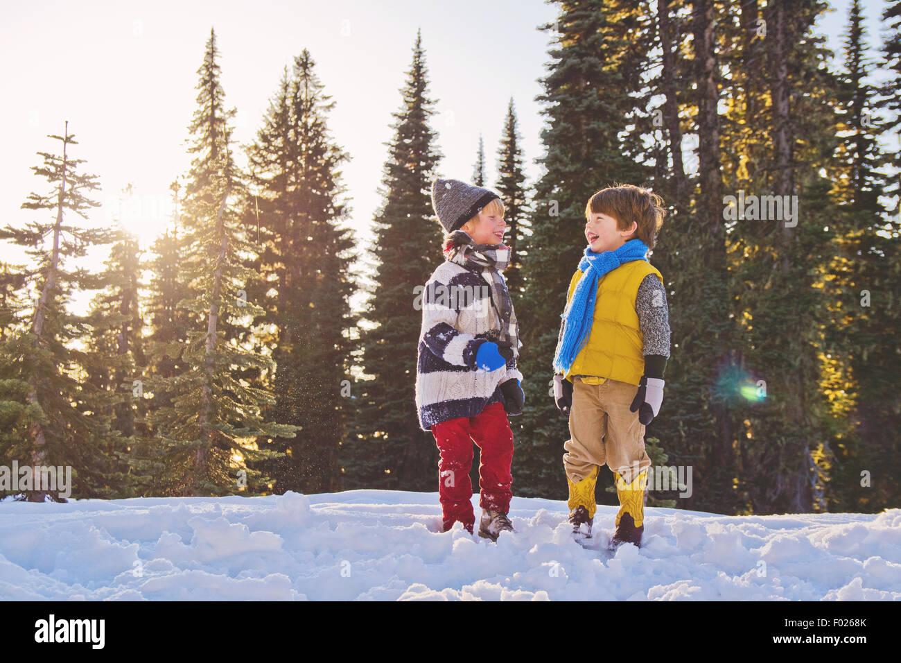 Dos niños riendo en la nieve, los árboles en el fondo Imagen De Stock