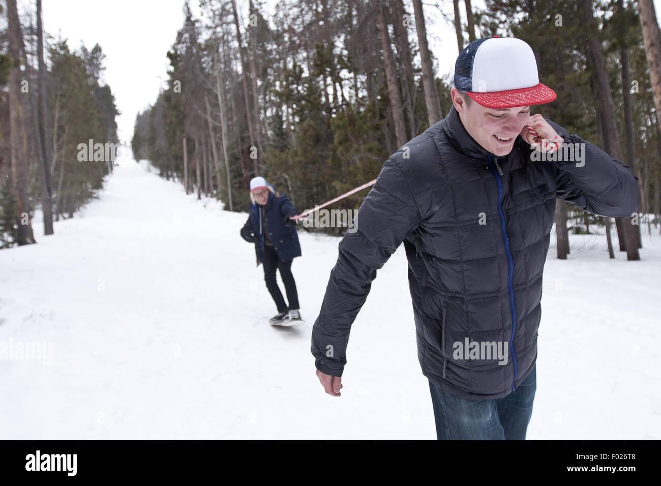 Joven hombre tirando en snowboard con cuerda Imagen De Stock