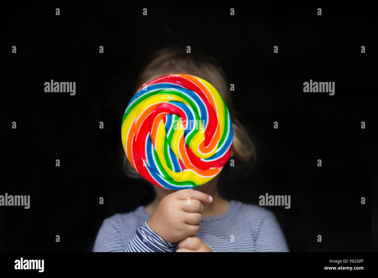 Retrato de una chica sujetando una piruleta multicolor Imagen De Stock