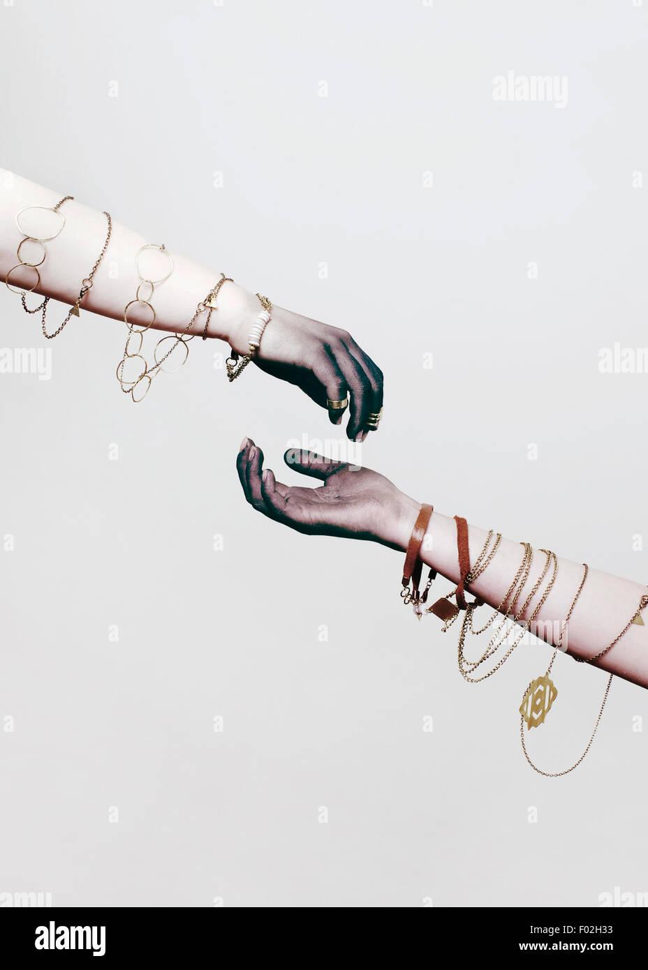 Dos brazos con joyas envuelto alrededor de ellos Imagen De Stock