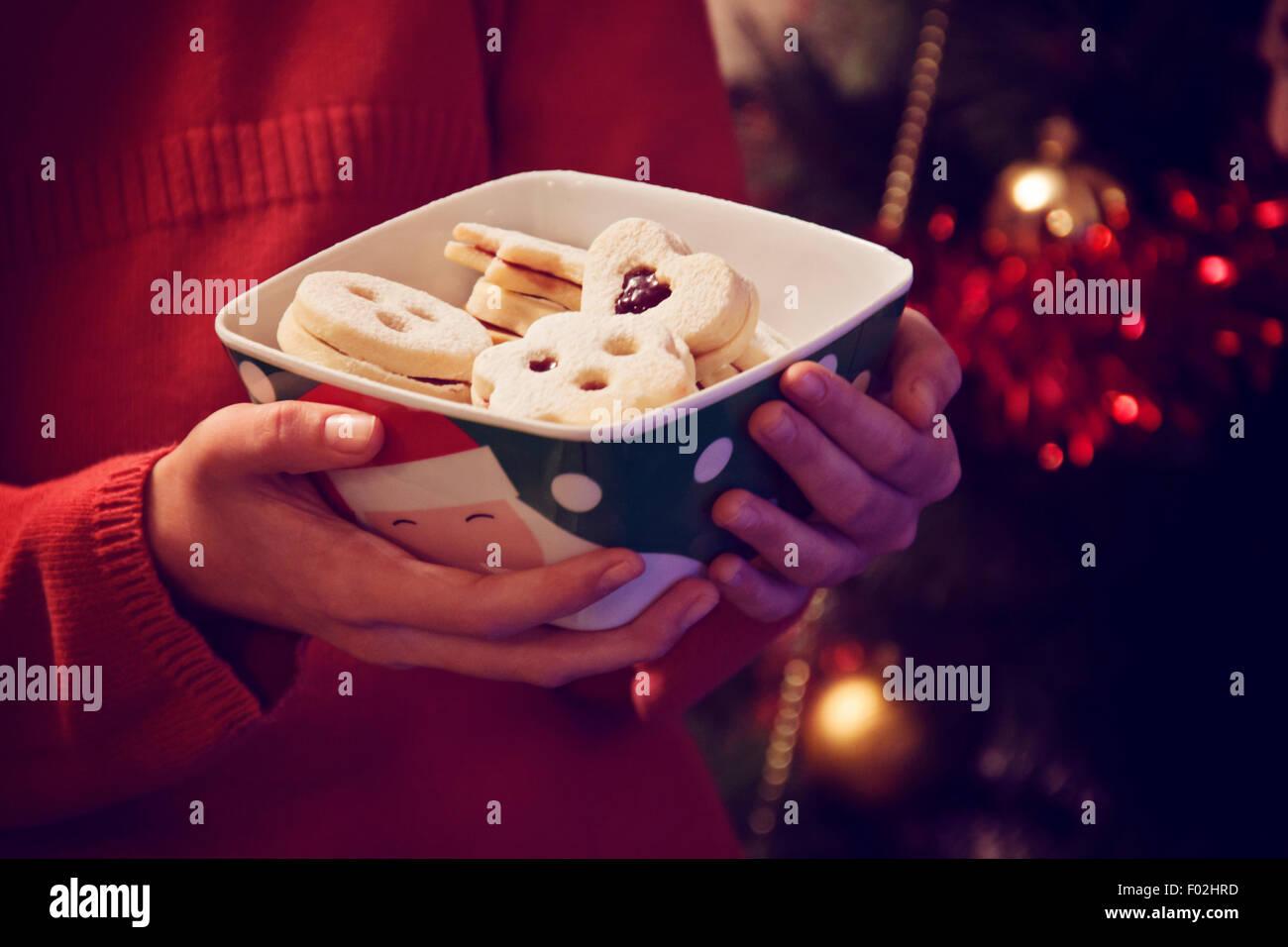 Chica sujetando el tazón con galletas de Navidad Imagen De Stock