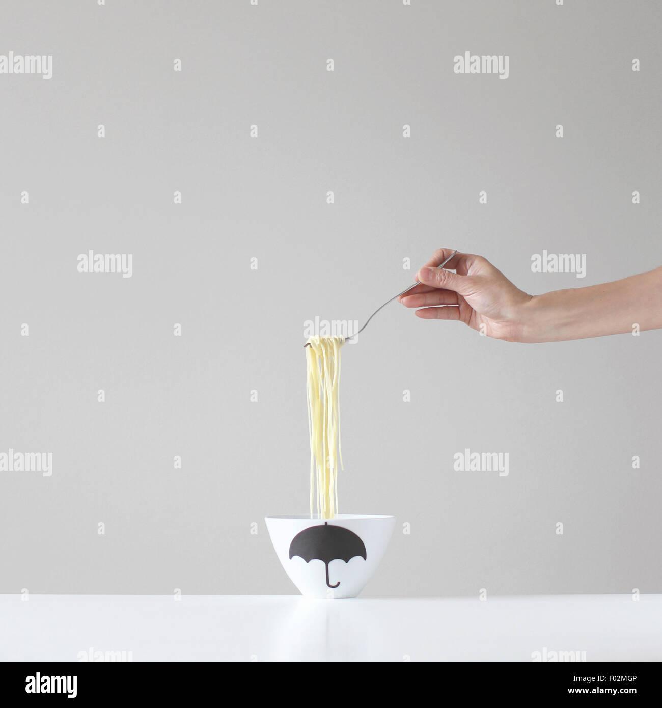 Mano sujetando un forkful de espaguetis sobre un tazón Imagen De Stock