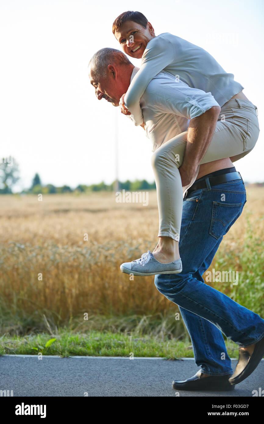 Viejo hombre mujer dando piggyback ride sobre su espalda en verano Foto de stock