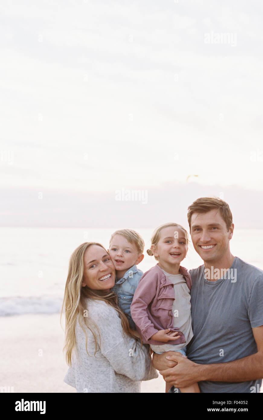 Par de pie con su hijo e hija en una playa de arena a la orilla del mar, mirando a la cámara, sonriendo. Imagen De Stock