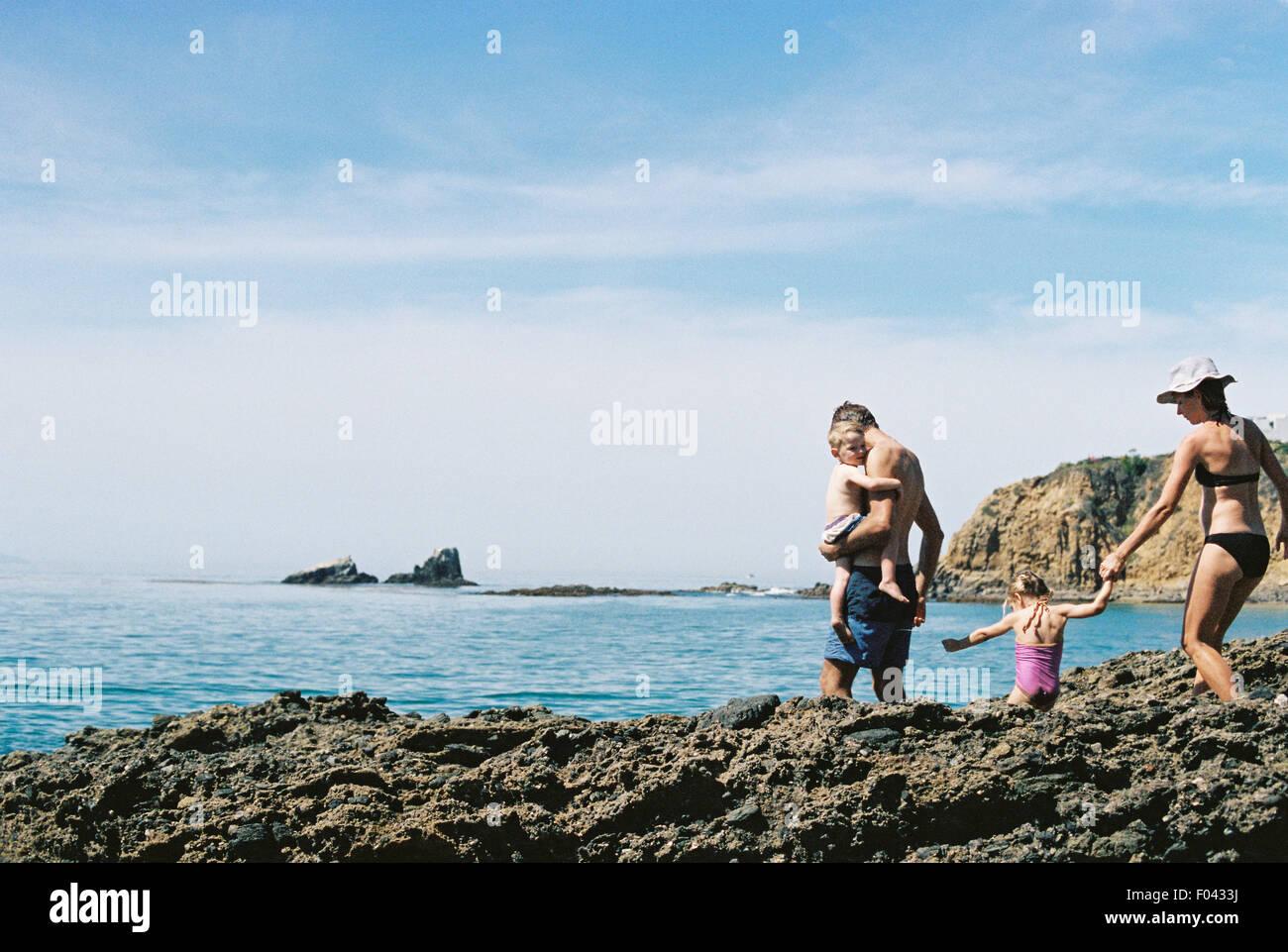 Una familia de vacaciones, dos adultos con su hijo e hija caminando a través de rocas por el océano. Imagen De Stock