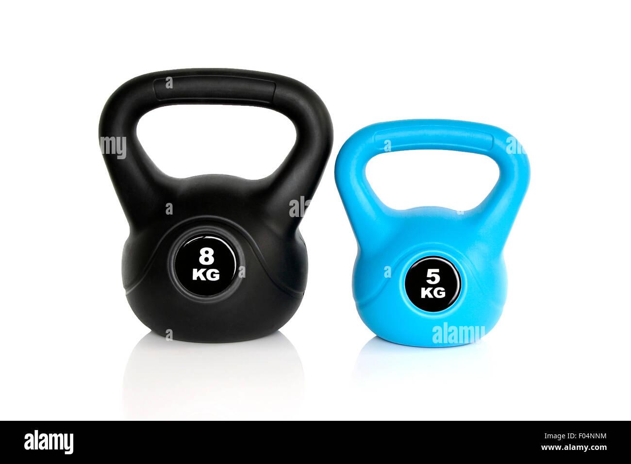 Un par negro de 8 kg y 5 kg kettlebell kettlebell azul aislado sobre fondo blanco. Los pesos para un entrenamiento físico. Foto de stock