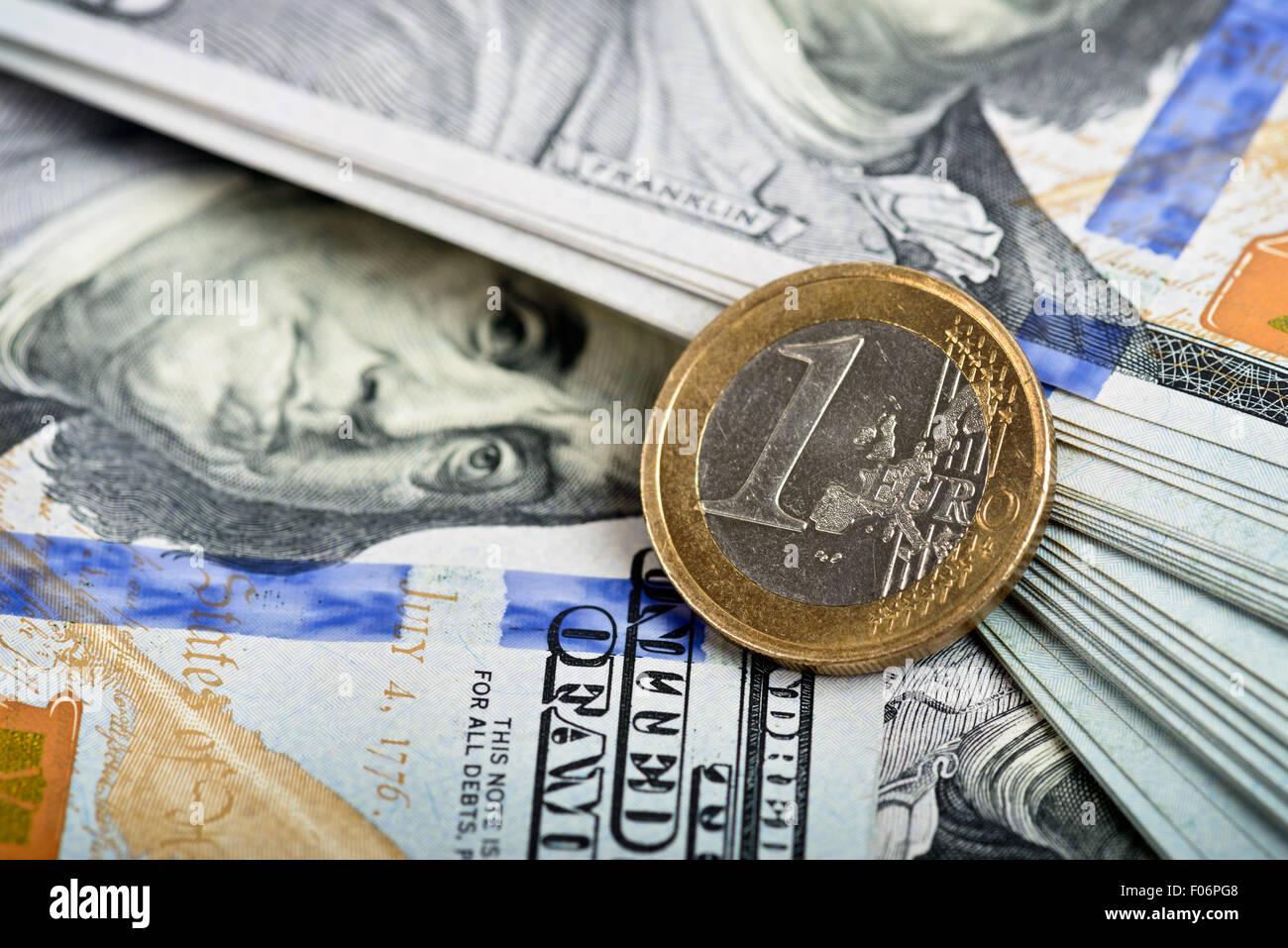 Detalle de una moneda de euro, dólar más notas en segundo plano. Imagen De Stock