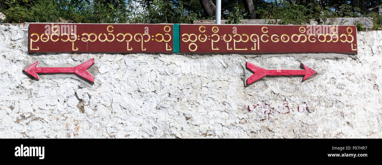Las señales de la carretera en birmano script con flechas apuntando a pagodas en cualquier dirección.En Imagen De Stock