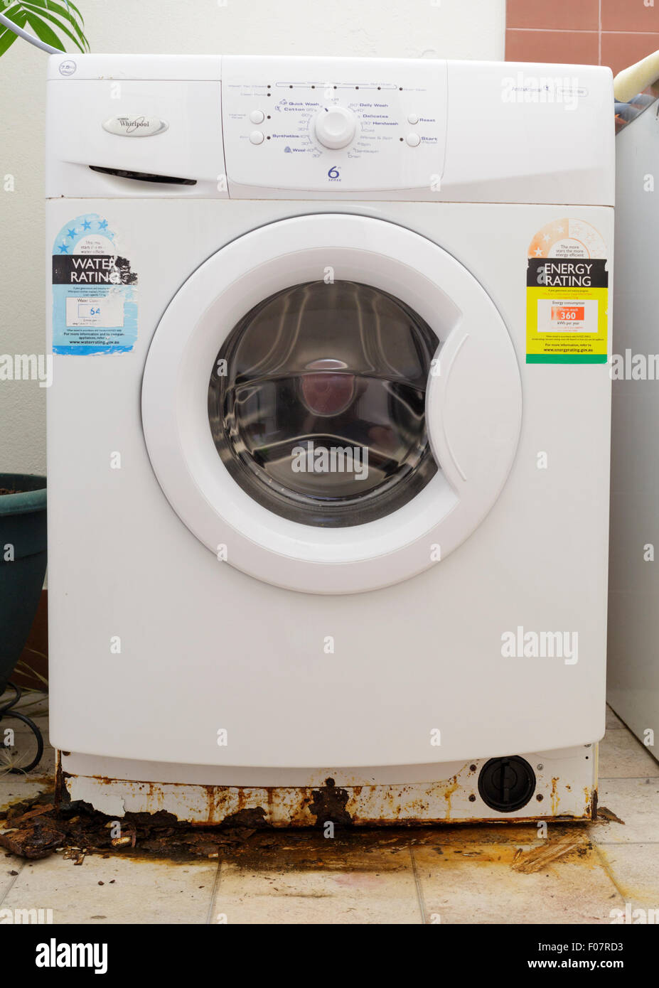 Una fuga en una lavadora con grandes manchas de óxido en la base. Imagen De Stock