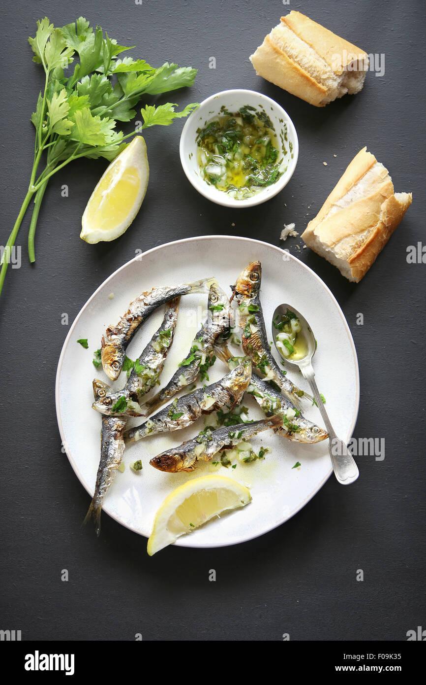 La sardina asada con salsa verde en un plato.vista superior Imagen De Stock