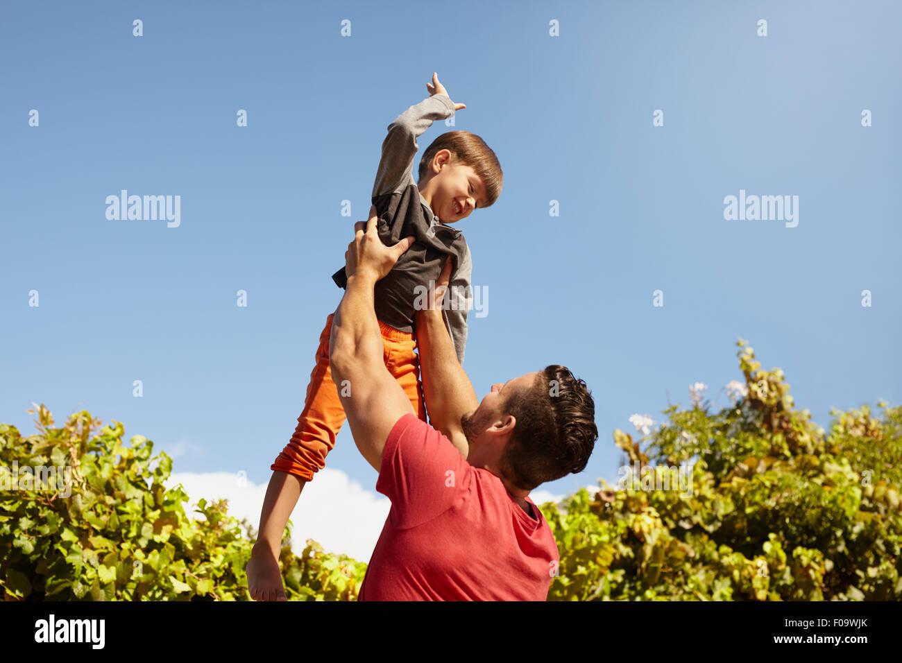 Foto de joven sosteniendo a su pequeño hijo en alto en el aire contra el cielo en un día soleado. Feliz Imagen De Stock