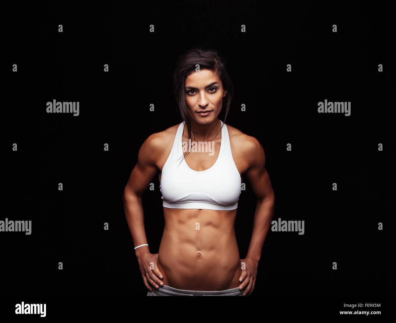 Retrato de estudio de una joven mujer deportiva aislado sobre fondo negro. Seguro modelo de fitness con abdomen Imagen De Stock