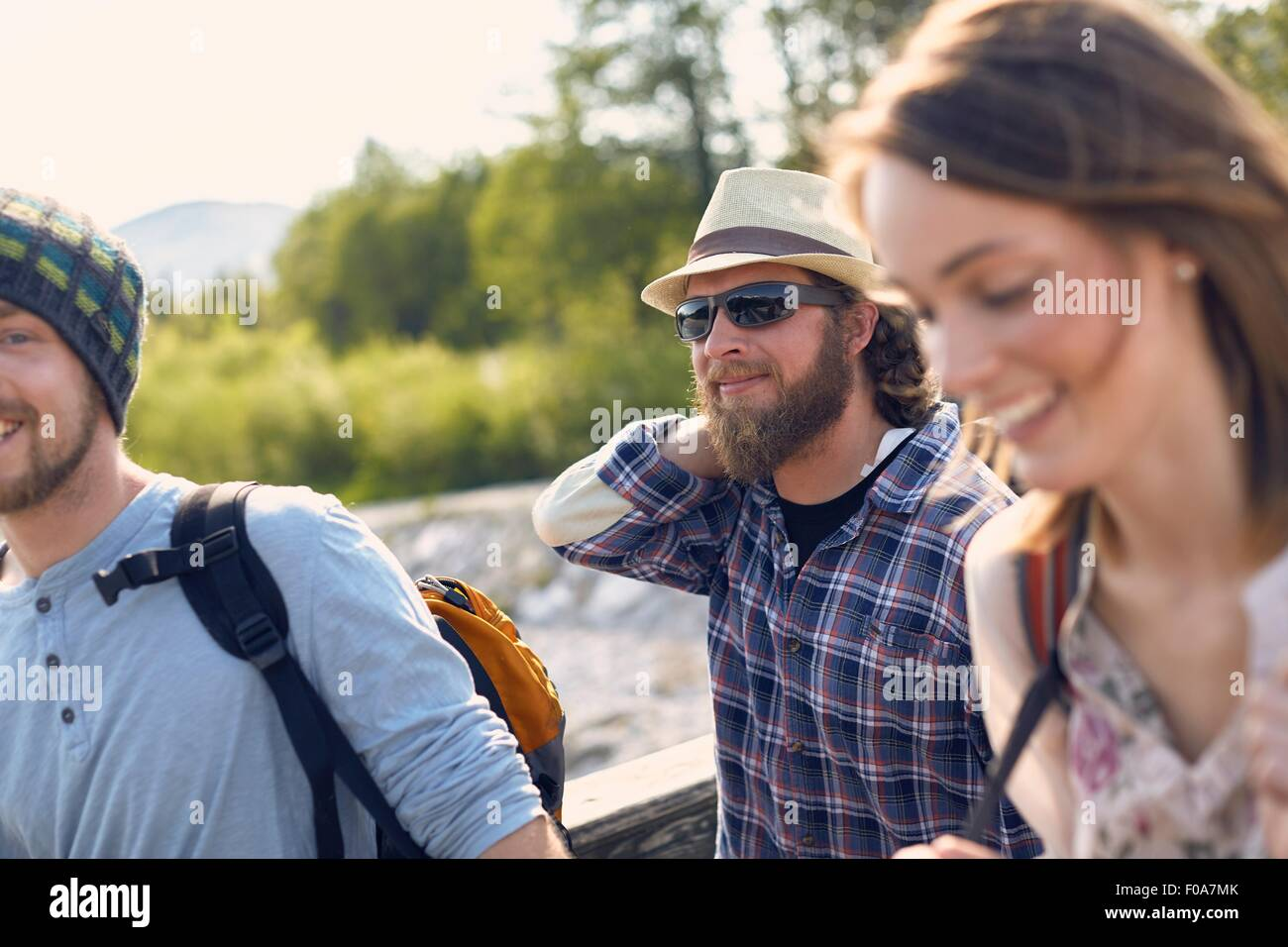 Tres personas caminando juntos portando mochilas, sonriendo Imagen De Stock