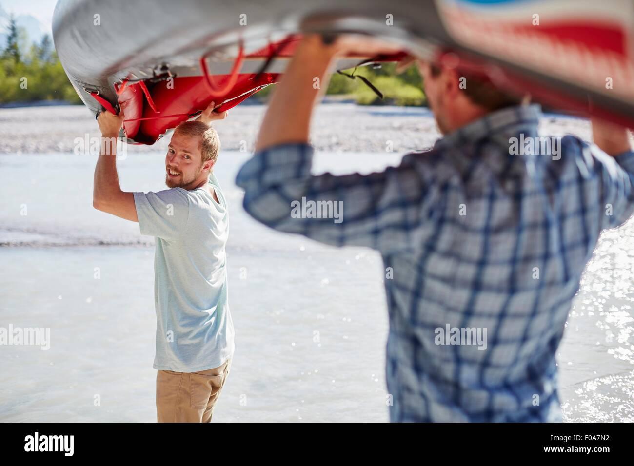 Vista trasera de dos hombres que llevaban balsa por encima de sus cabezas al agua Foto de stock