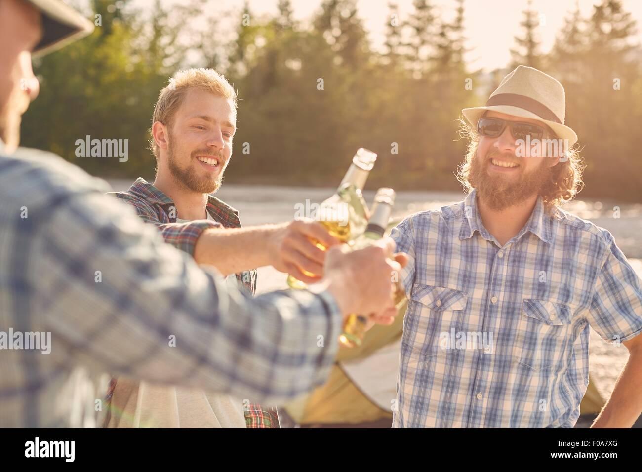 Los hombres hacer un brindis con las botellas de cerveza, sonriendo Imagen De Stock