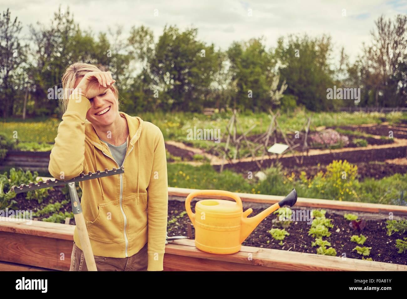 Mujer madura, jardinería, apoyándose en el rastrillo, riendo Imagen De Stock