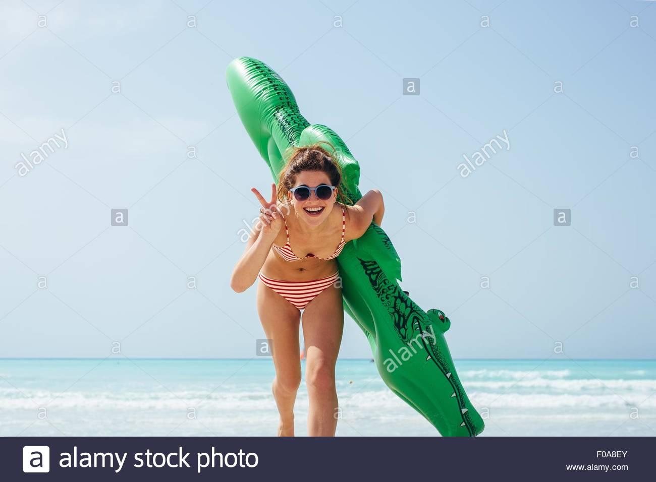 Retrato de joven mujer vistiendo bikini con cocodrilo inflable en la costa Imagen De Stock