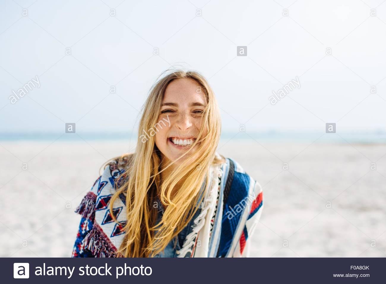 Retrato de mujer joven envuelta en una manta haciendo cara sonriente en la playa Imagen De Stock