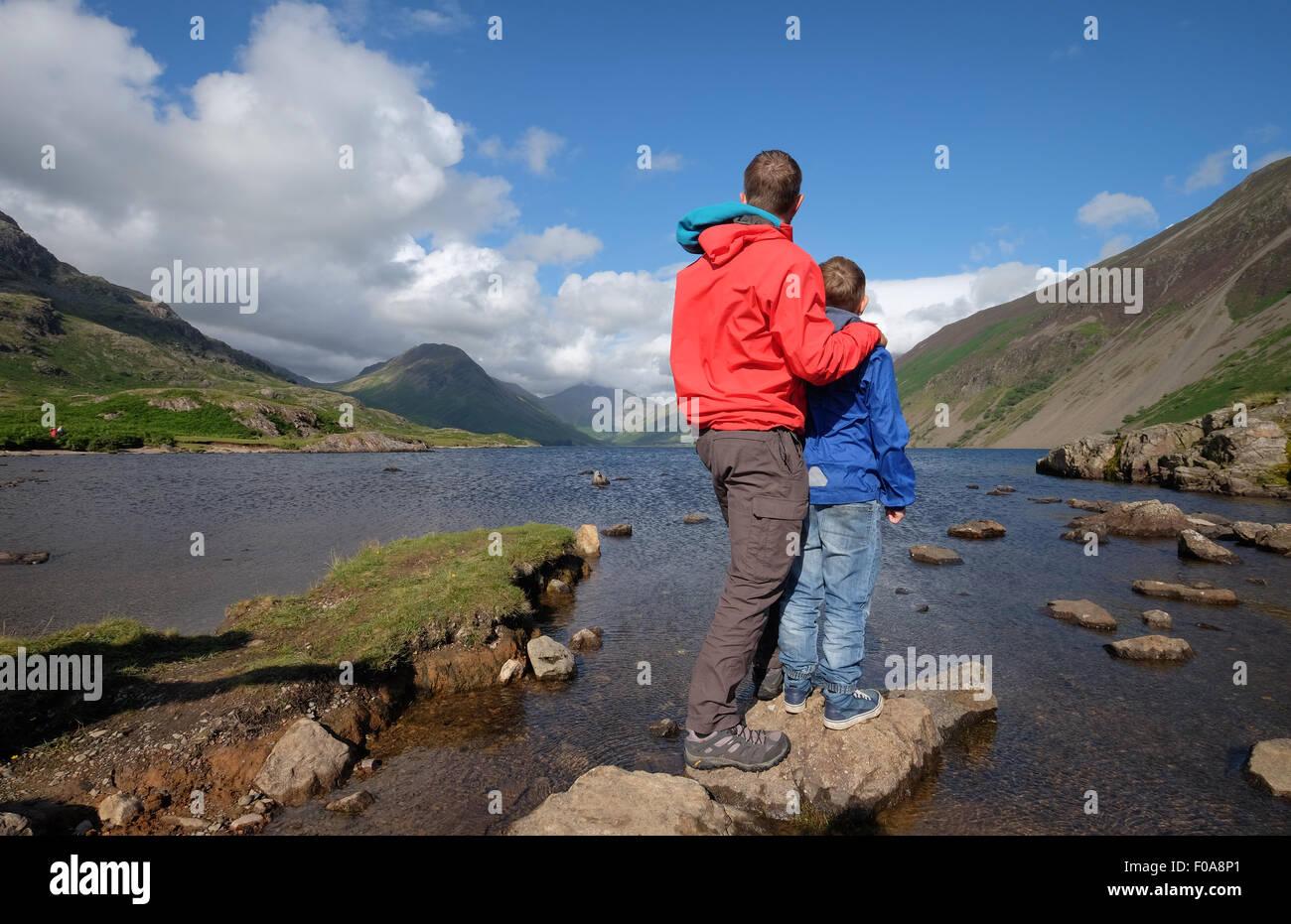 Un padre y su hijo disfrute de la vista en el agua residual en el distrito de los lagos de Cumbria, Reino Unido Imagen De Stock