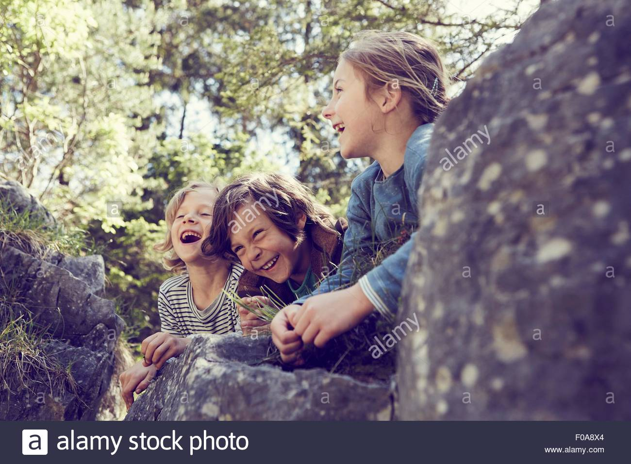 Tres niños sentados en las rocas en el bosque, riendo Imagen De Stock