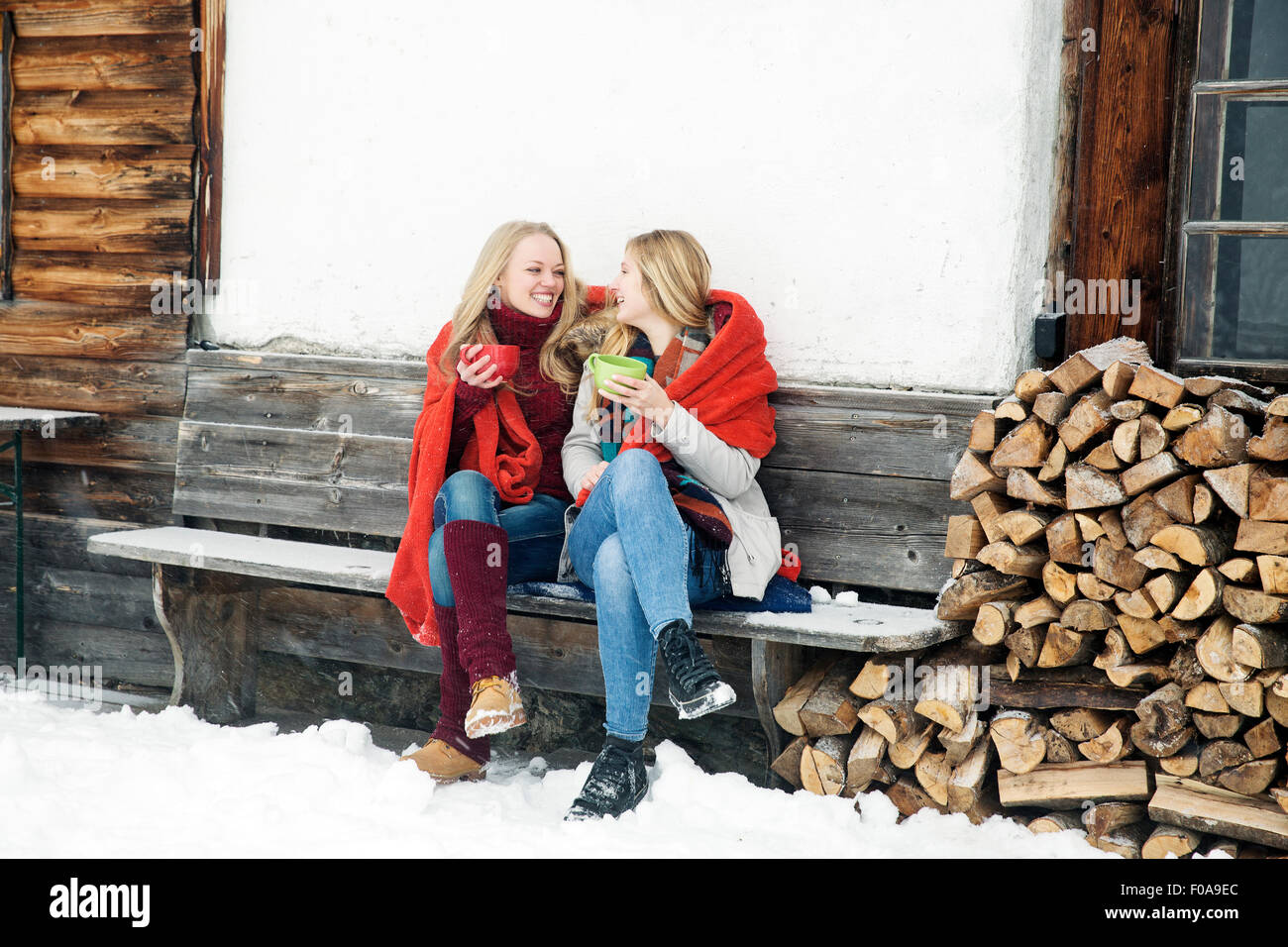 Dos amigas jóvenes bebiendo café fuera de cabaña de madera Imagen De Stock