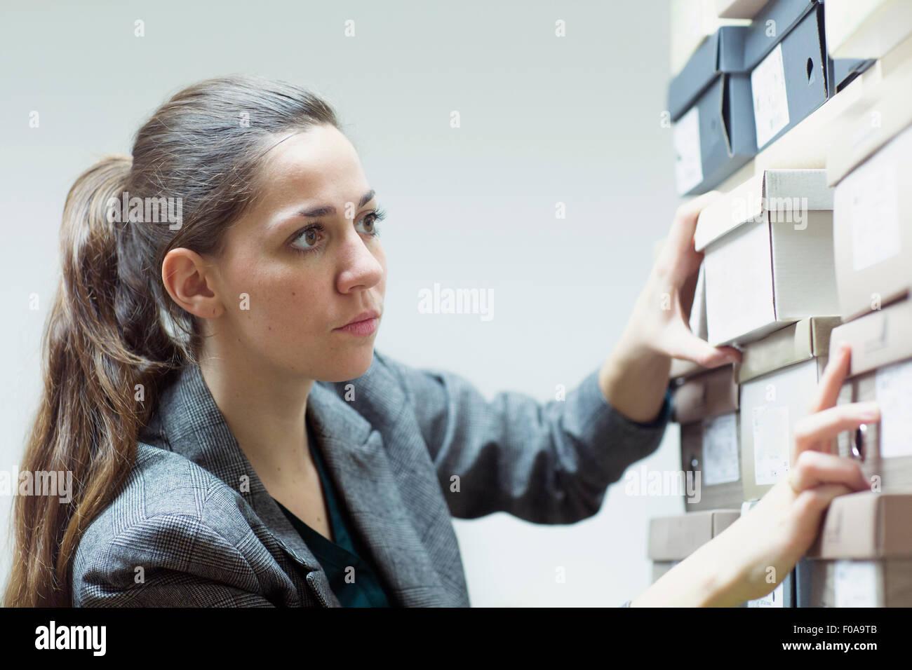 Asistente de ventas femenino buscando caja de zapatos en la zapatería stockroom Imagen De Stock