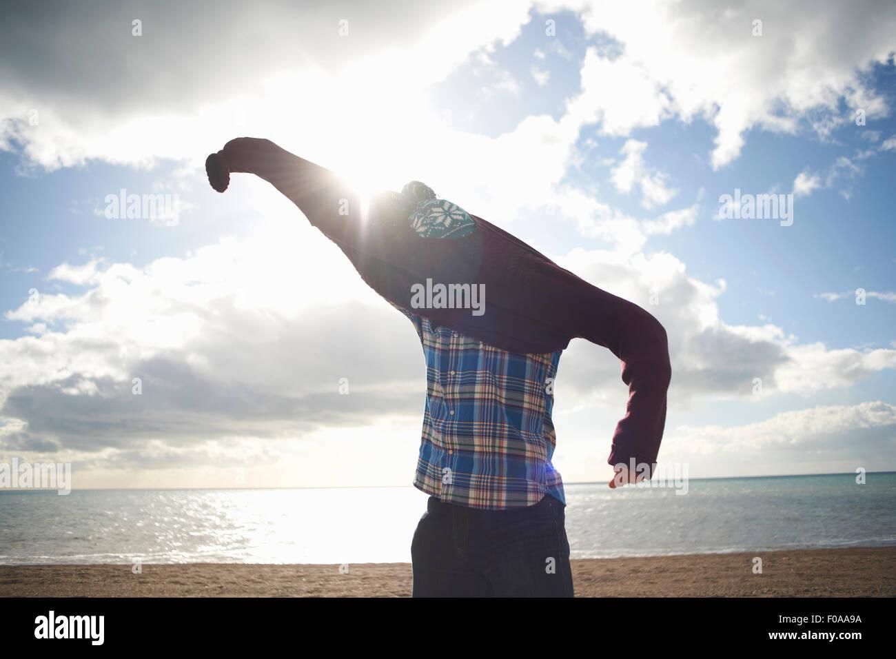 Hombre maduro, luchando para poner el suéter en la playa Foto de stock