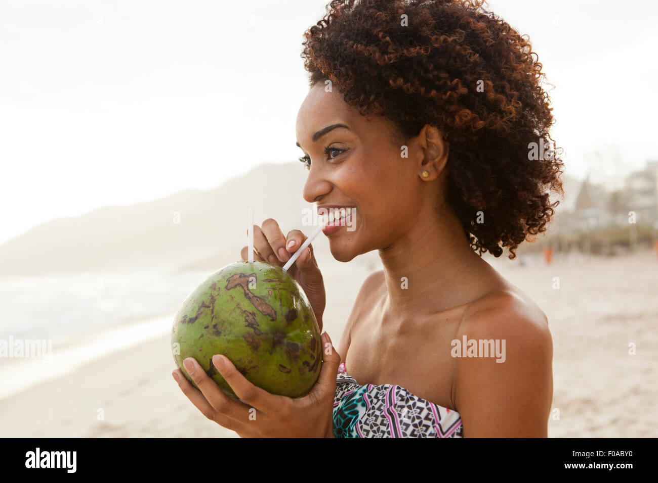 Retrato de mujer joven beber leche de coco en la playa, Río de Janeiro, Brasil Imagen De Stock