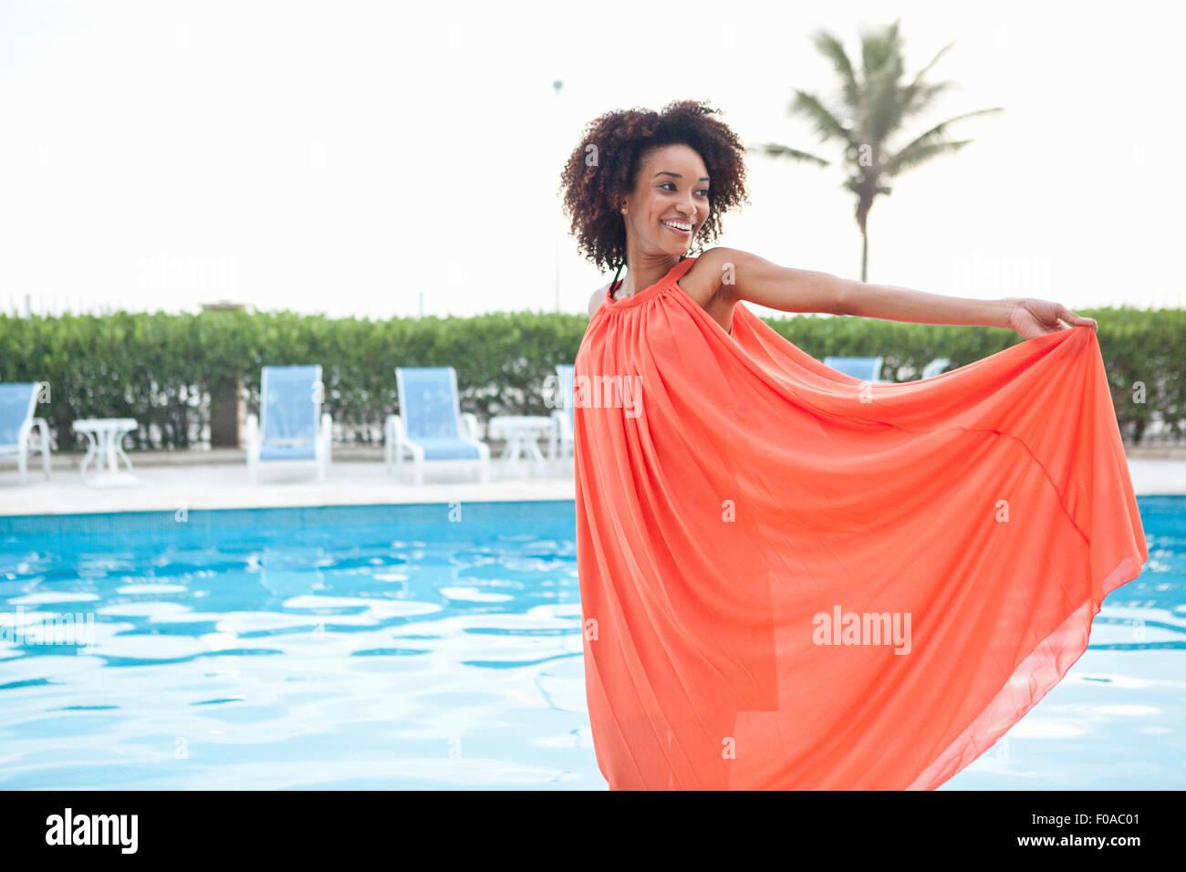 Retrato de mujer joven luciendo vestidos de naranja en el hotel al lado de la piscina, Rio de Janeiro, Brasil Imagen De Stock