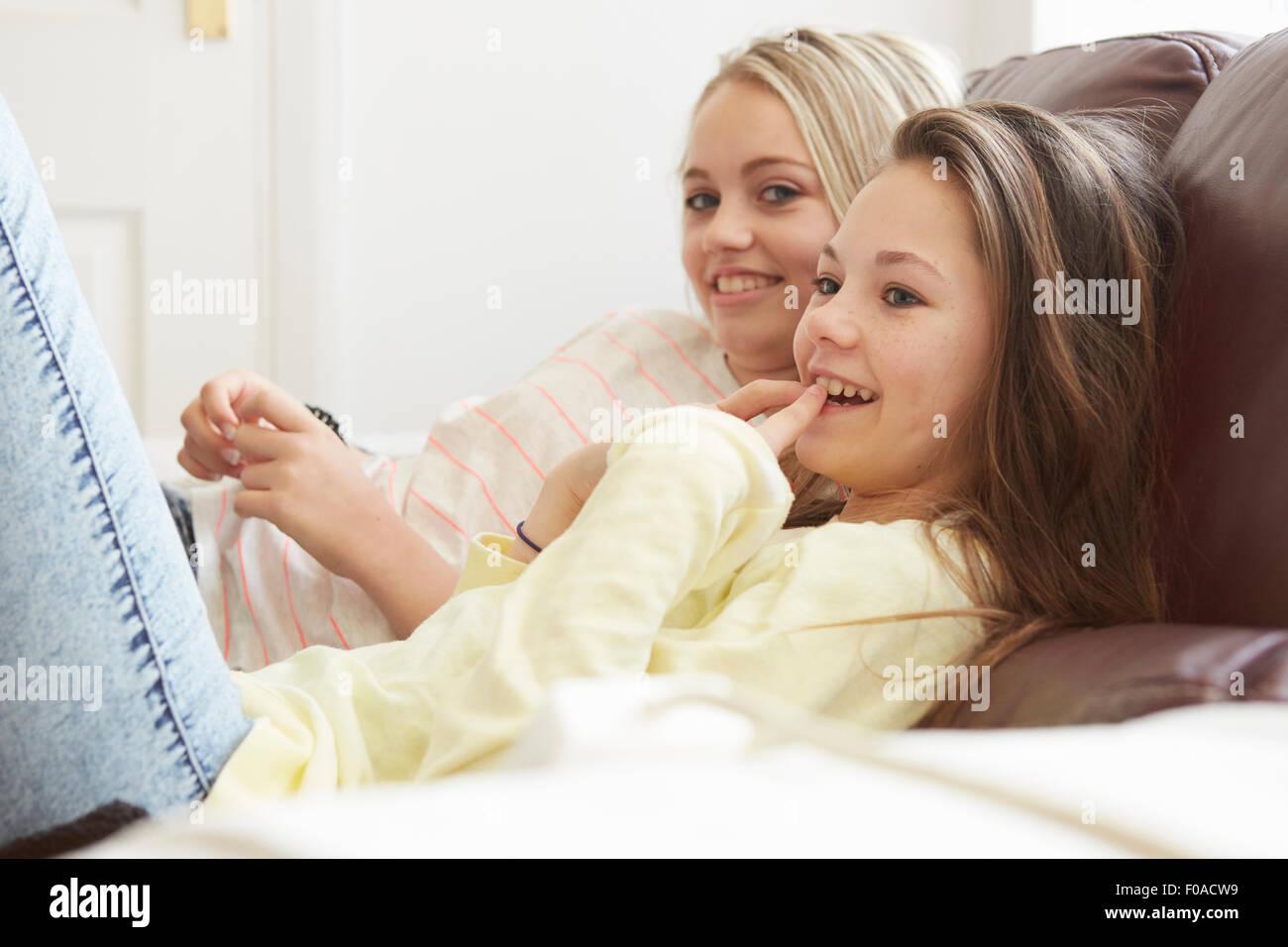 Dos niñas viendo la televisión desde el sofá Foto de stock