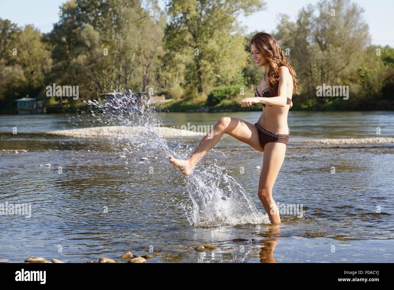 Mujer joven vistiendo un bikini salpicaduras y jugando en el río. Imagen De Stock