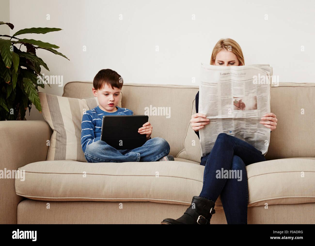 Joven utilizando tablet digital, madre la lectura de periódicos Foto de stock